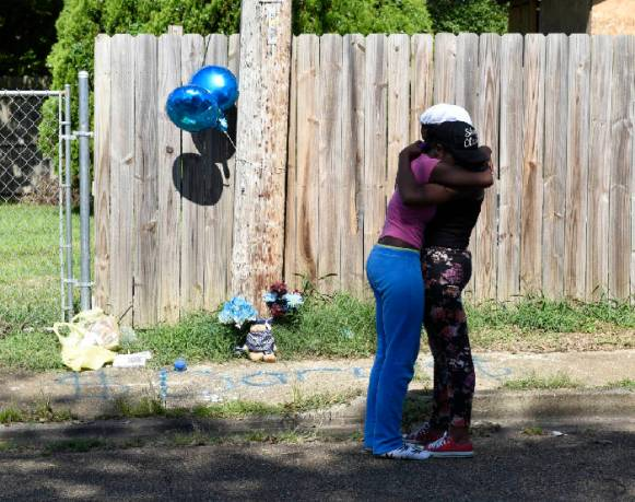 Jala Smith, left, and Asia Smith embrace at a roadside memorial on Wednesday, Aug. 26, 2015, in Chattanooga, Tenn., in the aftermath of a Tuesday night shooting in the 800 block of North Willow Street that killed their brother, 20-year-old Frederick Jordan Clark. Photo by John Rawlston /Times Free Press.
